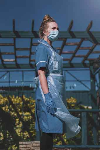 A medical assistant wearing PPE stood outside.